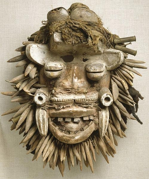 This African face mask, which appears to represent a bush spirit, contains animal and human composits. This mask combines many diverse materials to create an image of power. Multiple eyes, warthog tusks, large teeth, and other power symbols such as rifle casings and a beard of authentic and wooden leopard's teeth form a fierce countenance that frightens away negative forces.
